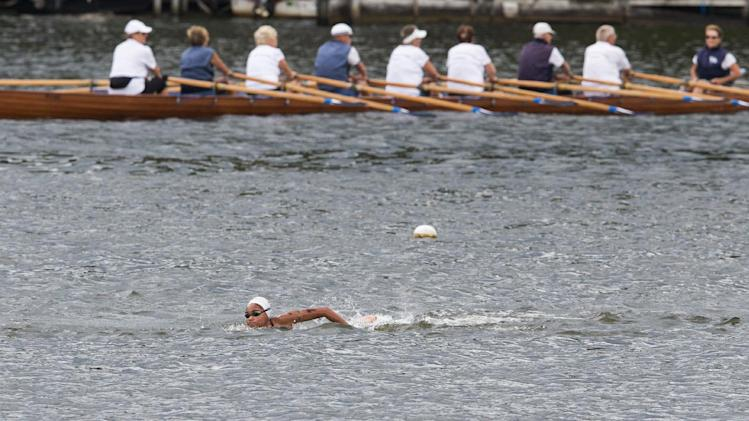 A rowing boat is seen behind Britain's Alice Dearing in the women's 5km open water swim competition at the LEN Swimming European Championships in Berlin, Germany, Thursday, Aug. 14, 2014