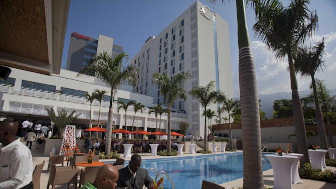 People eat near the pool at the new Marriott hotel after the hotel's opening ceremony in Port-au-Prince, Haiti, Tuesday, Feb. 24, 2015. Haiti's second international-branded hotel opened Tuesday in what backers of the project and officials hope will be a spur to further economic development in the impoverished country. (AP Photo/Dieu Nalio Chery)