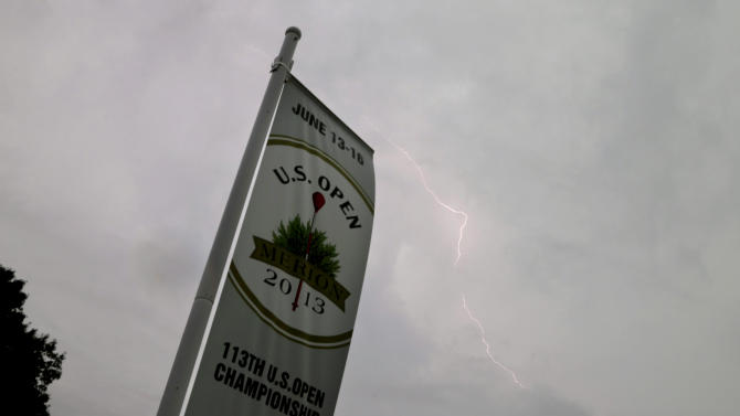Lightning flashes in the sky as a weather warning delays the first round of the U.S. Open golf tournament at Merion Golf Club, Thursday, June 13, 2013, in Ardmore, Pa. (AP Photo/Morry Gash)