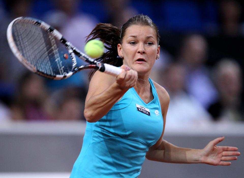 Poland's Agnieszka Radwanska hits a forehand against Belarus' Victoria Azarenka during their semifinal match at the Porsche Tennis Grand Prix in Stuttgart, Germany, Saturday, April 28, 2012.  Azarenka won 6-1, 6-3 to reach Sunday's final.(AP Photo/Michael Probst)