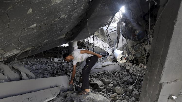 A Palestinian searches the ruins of the Al-Tawfeeq mosque after it was hit by an Israeli missile strike in the Nuseirat refugee camp, central Gaza Strip, Saturday, July 12, 2014. Palestinian officials said Israeli airstrikes in Gaza hit a mosque and a center for the disabled where two women were killed Saturday, raising the Palestinian death toll to more than 120, in an offensive that showed no signs of slowing down. (AP Photo/Hatem Moussa)