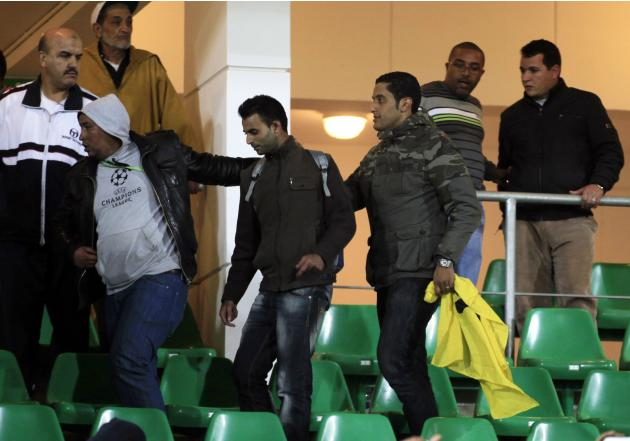 Police escort a fan during the FIFA Club World Cup soccer match between Morocco's Raja Casablanca and Mexico's Monterrey in Agadir
