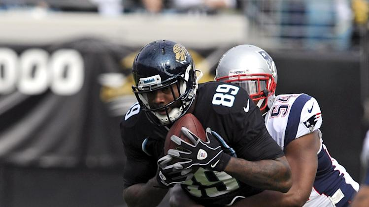 Jacksonville Jaguars tight end Marcedes Lewis (89) catches a pass as he is tackled by New England Patriots outside linebacker Dont'a Hightower (54) during the first half of an NFL football game on Sunday, Dec.  23, 2012, in Jacksonville, Fla. (AP Photo/Stephen Morton)