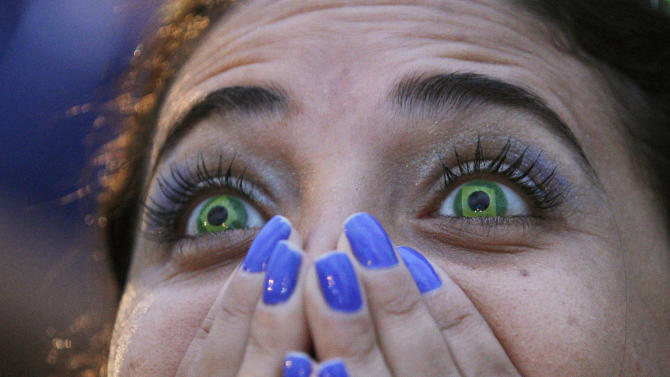 A Brazil soccer fan wearing contact lenses that mimic the Brazilian flag reacts as she watches her team play Germany in a World Cup semifinal game via live telecast inside the FIFA Fan Fest area on Copacabana beach in Rio de Janeiro, Brazil, Tuesday, July 8, 2014. (AP Photo/Leo Correa)