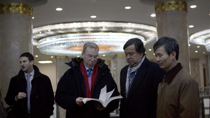 """Executive Chairman of Google, Eric Schmidt, second from left, and former Governor of New Mexico Bill Richardson, second from right,  look through an information technology text book at the Grand People's Study House in Pyongyang, North Korea on Wednesday, Jan. 9, 2013. At left is director of Google Ideas think tank, Jared Cohen. The textbook is titled """"Aries Net+ Certified Technician First Edition Version 3.0. """" (AP Photo/David Guttenfelder)"""