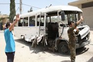 A Syrian soldier signals as he stands close a damaged bus following an explosion which killed there people near Damascus