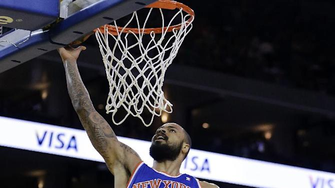 New York Knicks' Tyson Chandler (6) lays up a shot over Golden State Warriors' Harrison Barnes (40) and Andrew Bogut, right,  during the first half of an NBA basketball game Monday, March 11, 2013, in Oakland, Calif. (AP Photo/Ben Margot)