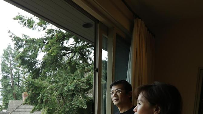 Janie Lee, right, a residential specialist with John L. Scott Real Estate, shows a home for sale to her client, Hongbin Wei, left, of Beijing, China, Thursday, Dec. 18, 2014, in Medina, Wash., near Seattle. Real estate agents such as Lee are taking note of growing connections linking China and Washington state, which ranks second to California in real estate sales to Chinese buyers. (AP Photo/Ted S. Warren)