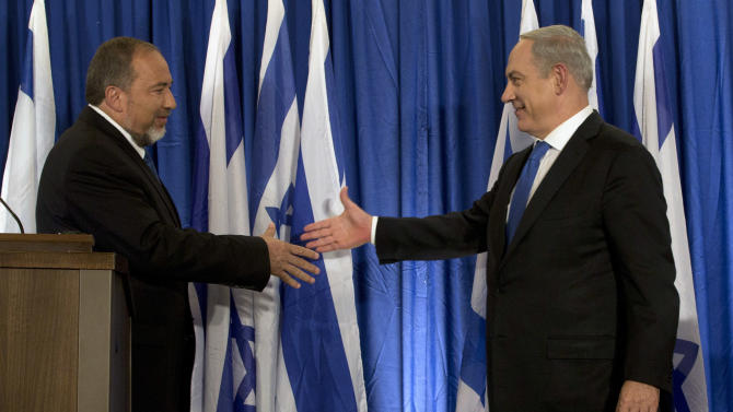 Israeli Prime Minister Benjamin Netanyahu, right, and Israel's Foreign Minister Avigdor Lieberman shake hands in front of the media after giving an statement in Jerusalem, Thursday, Oct. 25, 2012. Netanyahu said his Likud Party will join forces with the hard-line party of his Foreign Minister in upcoming parliamentary elections. (AP Photo/Bernat Armangue)