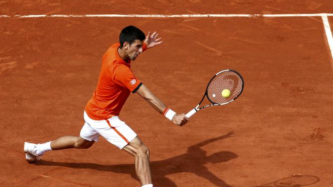 Novak Djokovic of Serbia plays a shot to Gilles Muller of Luxemourg during their men's singles match at the French Open tennis tournament at the Roland Garros stadium in Paris