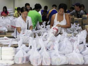 Volunteers prepare relief goods, to be delivered before …