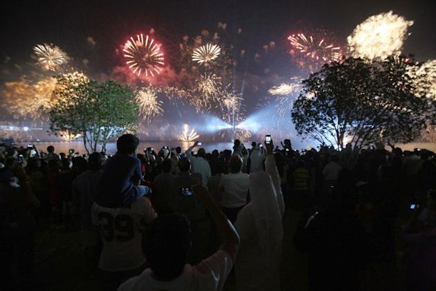 People look on as fireworks light the sky near the Kuwait Towers during celebrations marking the Gulf state's 50th anniversary of its constitution, in Kuwait City on November 10, 2012.  Kuwait marked