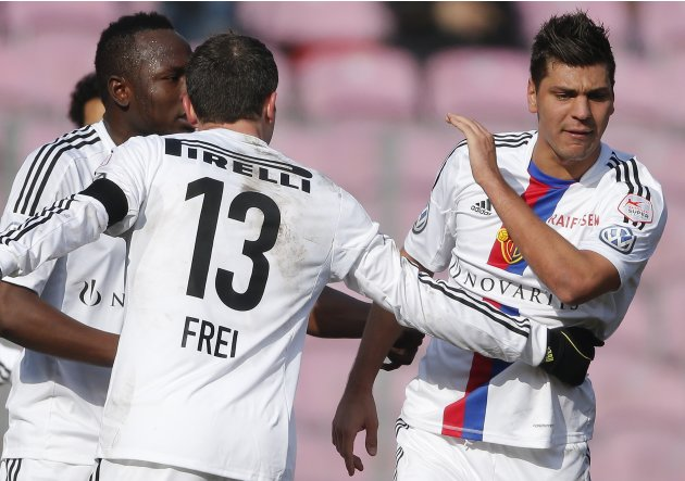 FC Basel's Dragovic reacts to receiving a red card as his teammates Frei and Daogari walk him out of the pitch during his Swiss Super League soccer match against FC Servette in Geneva