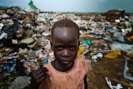 A young child scavanges for food at a rubbish dump in the South Sudanese capital Juba on August 1. The increase of prices in South Sudan makes life very difficult for South Sudanese people, some of them have no other choice but to pick up food or find and sell iron from rubbish dumps