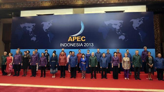 Asia-Pacific Economic Cooperation (APEC) leaders and their spouses pose for a group photo at the APEC Summit Official Dinner in Nusa Dua