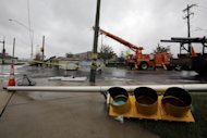 Crews work to remove a damaged sign in the wake of superstorm Sandy, Tuesday, Oct. 30, 2012, in Philadelphia. Millions of people from Maine to the Carolinas awoke Tuesday without power, and an eerily quiet New York City was all but closed off by car, train and air as superstorm Sandy steamed inland, still delivering punishing wind and rain.(AP Photo/Matt Slocum)