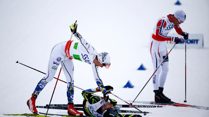 Sweden's Olsson takes care about Manificat of France after their handover in the men's cross country free/classic 4 x 10 km relay final at the Nordic World Ski Championships in Falun
