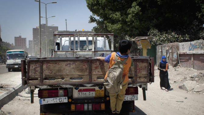 In this Wednesday, April 24, 2013 photo, an Egyptian boy takes a free ride by hanging on the gate of a passing pickup truck on a street in Cairo, Egypt. Egypt has been increasingly knocking on doors around the world seeking billions to fill rapidly draining coffers. But not everyone is eager to give, and economists fear that quick injections of cash only let the government put off painful economic reform. (AP Photo/Nasser Nasser)