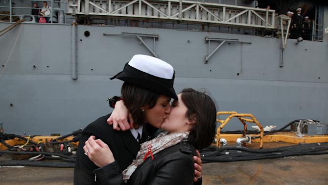 FILE - In this Dec. 22, 2011 file photo, Petty Officer 2nd Class Marissa Gaeta, left, kisses her girlfriend of two years, Petty Officer 3rd Class Citlalic Snell, at Joint Expeditionary Base Little Creek in Virginia Beach, Va., after Gaeta's ship returned from 80 days at sea. In the summer of 2011, gays in the military dared not acknowledge their sexual orientation. Now, just a year later, the Pentagon will salute them, marking June as gay pride month just as it has marked other celebrations honoring racial or ethnic groups. (AP Photo/Virginian-Pilot, Brian J. Clark, File)