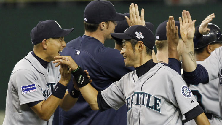 Seattle Mariners rightfielder Ichiro Suzuki, center, celebrates with teammate Munenori Kawasaki, left, after beating the Oakland Athletics 3-1 in their American League season opening MLB baseball game at Tokyo Dome in Tokyo, Wednesday, March 28, 2012. (AP Photo/Koji Sasahara)