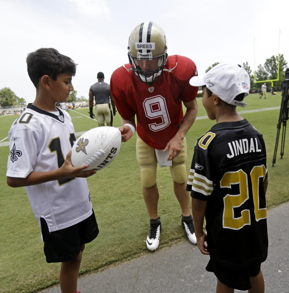 New Orleans Saints quarterback Drew Brees (9) signs autographs for Shaan Jindal, 11, left, and Slade Jindal, 9, sons of Louisiana Gov. Bobby Jindal, during their NFL football training camp in Metairie, La., Tuesday, July 30, 2013. (AP Photo/Gerald Herbert)