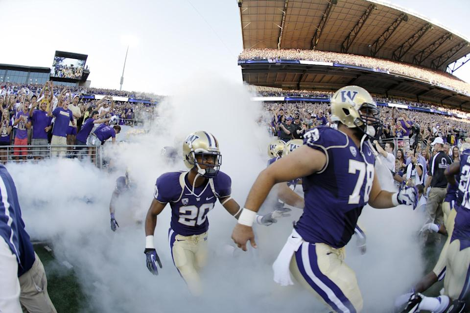 In this photo made with a fish-eye wide angle lens, Washington's Mike Criste (78) and Kevin King (20) run out of the tunnel into newly renovated Husky Stadium for an NCAA college football game against Boise State, Saturday, Aug. 31, 2013, in Seattle. (AP Photo/Ted S. Warren)