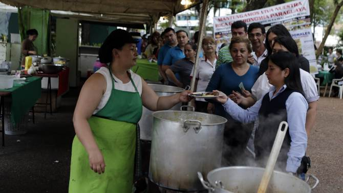 People queue to receive servings of a traditional dish called yopara during Karai Octubre celebrations in Asuncion