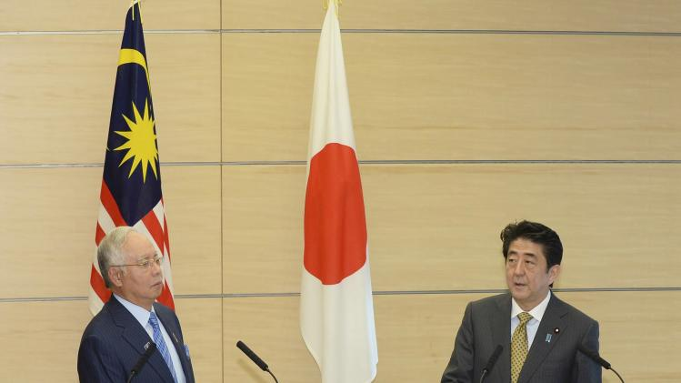 Japan's PM Abe listens to his Malaysian counterpart Razak during a media announcement after their talks at Abe's official residence in Tokyo