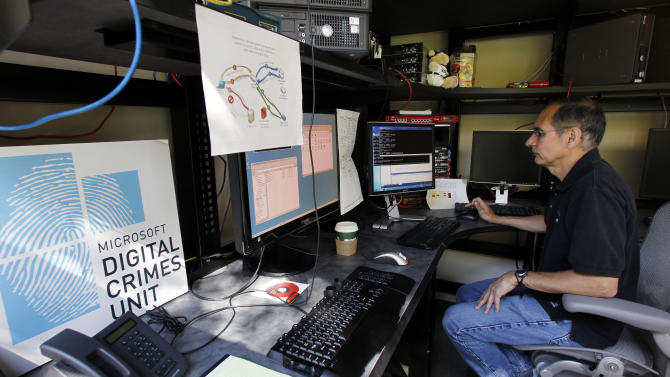 David Anselmi, a Microsoft senior manger of investigations in the company's Digital Crimes Unit, sits in the DCU lab there Wednesday, Sept. 12, 2012, in Redmond, Wash. Documents unsealed Thursday by a federal court in Virginia describe a new front in a legal campaign against cybercrime being waged by Microsoft. The company says evidence shows cybercriminals are now looking for opportunities to inject malicious software and code into counterfeit versions of computer operating systems even before the machines are wrapped in plastic and sold to unsuspecting customers. (AP Photo/Elaine Thompson)