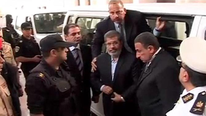 FILE - This Monday, Nov. 3, 2013 file image made from video provided by Egypt's Interior Ministry shows ousted President Mohammed Morsi,center, arriving for a trial hearing in Cairo, Egypt after four months in secret detention. Morsi had his first extensive meeting with lawyers, Tuesday, Nov. 12, 2013, consulting in prison with a team from his Muslim Brotherhood over his ongoing trial on charges of inciting murder. So far, Morsi is refusing to accept any legal representation in the trial, insisting he remains president, and his son says he wants to take legal action against those prosecuting him after his ouster by the military. (AP Photo/Egyptian Interior Ministry, File)