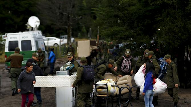 Policemen help to residents to move their belongings from an area damaged by lahar from Calbuco Volcano at Correntoso
