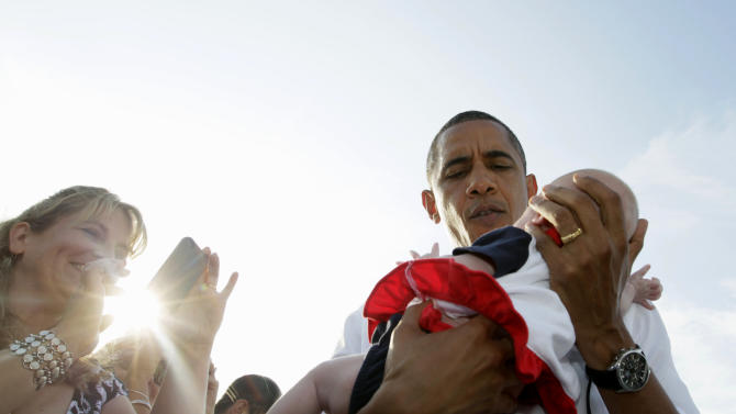 President Barack Obama holds a child wearing Boston Red Sox regalia, as he greets people on the tarmac upon his arrival at Cape Cod Coast Guard Air Station in Bourne, Mass., Thursday, Aug. 18, 2011.  (AP Photo/Carolyn Kaster)