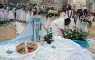 Women carry flower offerings for Iemanja on Copacabana beach, Rio de Janeiro, Brazil on December 29, 2012. Tens of thousands of people across Brazil on Saturday paid their annual tribute to Iemanja, the goddess of the sea in the Afro-Brazilian religion Candomble, offering flowers, food and perfume, as drums belted out African rhythms