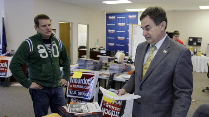 In this April 27, 2012, photo, Richard Mourdock, Indiana Treasurer and candidate for the U.S. Senate in the republican primary, talks with communications director Chris Conner at a campaign office in Indianapolis. Mourdock faces incumbent Richard Lugar in the primary. (AP Photo/Michael Conroy)