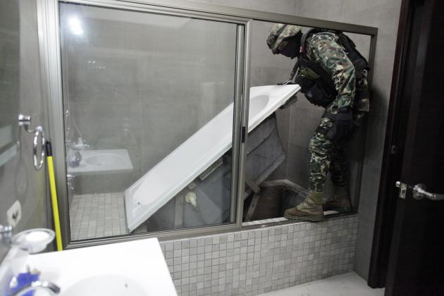 "A Mexican marine lifts a bathtub that leads to a tunnel and exits in the city's drainage system at one of the houses of Joaquin ""Chapo"" Guzman in Culiacan"