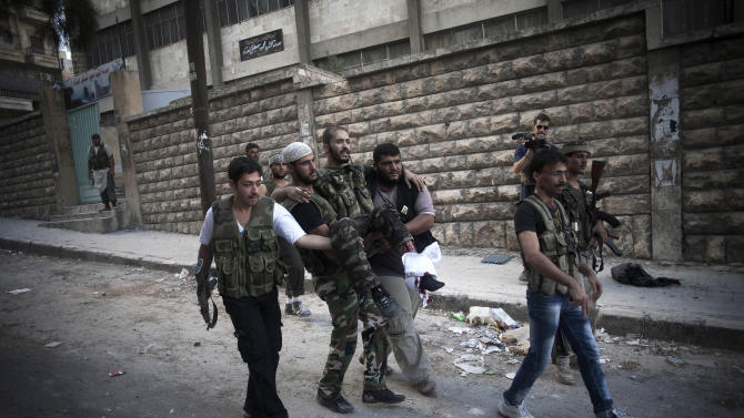 Free Syrian Army fighters carry a wounded comrade in the Izaa district in Aleppo, Syria, Tuesday, Sept. 11, 2012. (AP Photo/Manu Brabo)