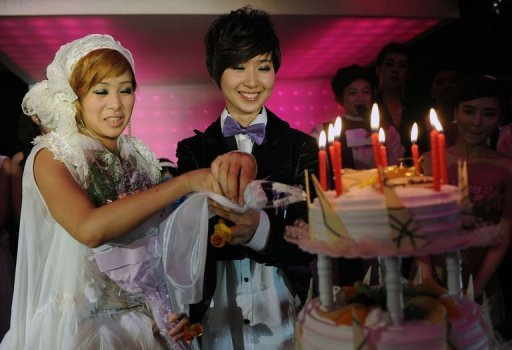 "A same sex couple cut a cake during a mass ""wedding"" party event in Taipei"