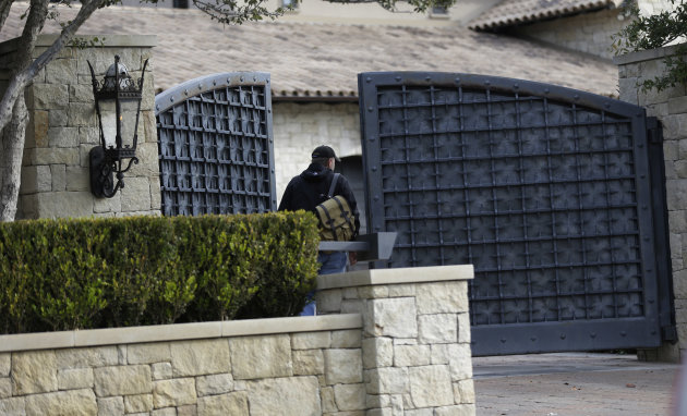 An unidentified man enters a gate at the home of cyclist Lance Armstrong, Monday, Jan. 14, 2013, in Austin, Texas. After more than a decade of denying that he doped to win the Tour de France seven tim