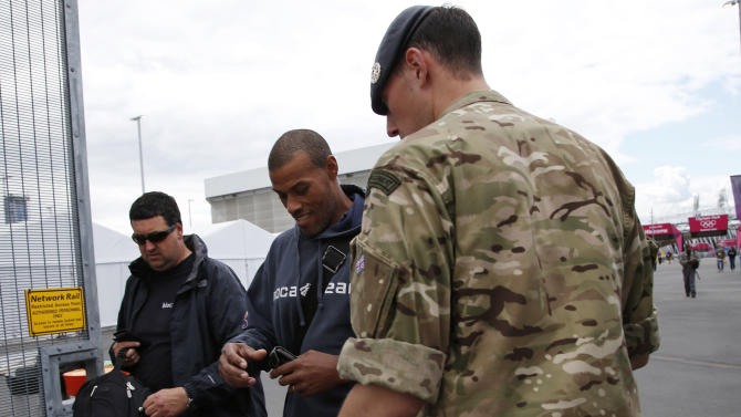 A British soldier checks identification cards at the entrance to the Olympic Park as preparations continue for the 2012 Summer Olympics, Sunday, July 15, 2012, in London. (AP Photo/Jae Hong)