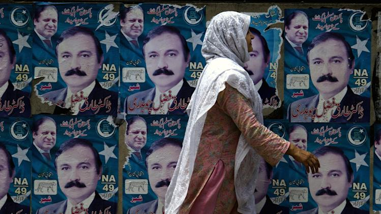 A Pakistani woman walks past posters of a parliamentary election candidate in Islamabad, Pakistan, Monday, April 29, 2013. Candidates restricted their election campaigns to corner meetings and social media due to ongoing attacks by Taliban on their offices and rallies of various political parties. (AP Photo/B.K. Bangash)