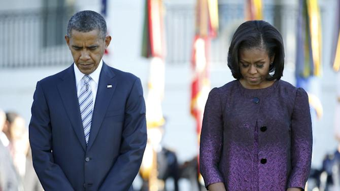 President Barack Obama and first lady Michelle Obama, joined by members of the White House staff pause during a moment of silence to mark the 11th anniversary of the Sept, 11th, Tuesday, Sept. 11, 2012, on the South Lawn of the White House in Washington. (AP Photo/Carolyn Kaster)