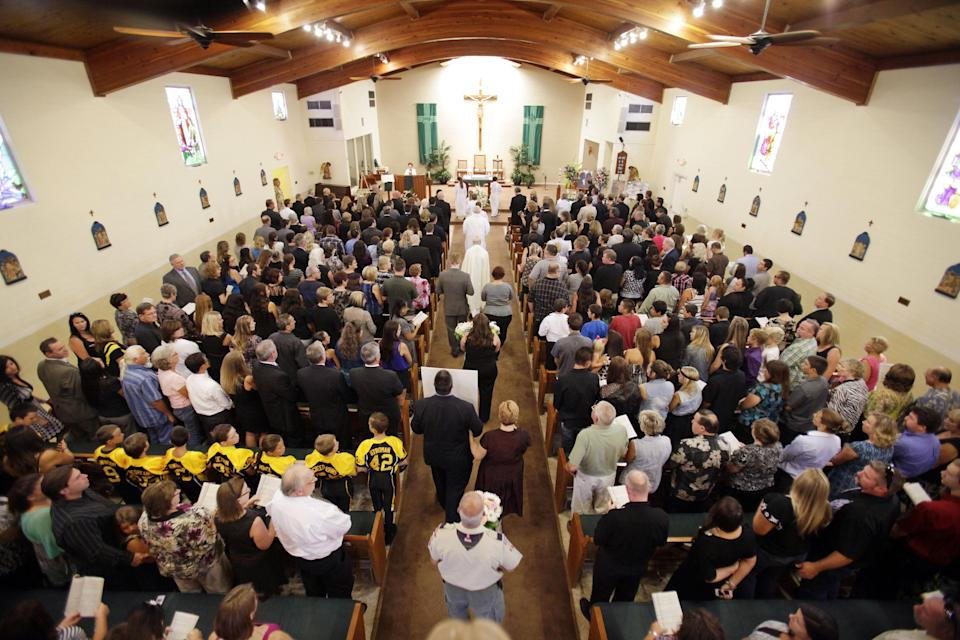 The memorial service for Christina Anderson and Ethan Anderson begins at Guardian Angels Catholic Church on Saturday Aug. 24, 2013 in Santee, Calif. The pair was found at the home of James Lee DiMaggio, who set it ablaze earlier this month. (AP Photo/U-T San Diego, Howard Lipin, Pool)