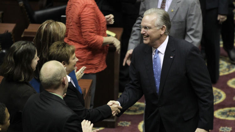 FILE - Inthis Jan. 28, 2013 file photo Missouri Gov. Jay Nixon shakes hands with lawmakers before deliver the annual State of the State address in Jefferson City, Mo. When it comes to money in politics, the sky is the limit in Missouri where ethics laws are the weakest in the nation, according to Nixon. Nixon vowed during his address to push a ballot initiative to reinstate campaign contribution limits if lawmakers won't do it themselves this year. (AP Photo/Jeff Roberson, File)