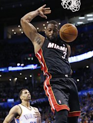 Miami Heat guard Dwyane Wade (3) dunks in front of Oklahoma City Thunder guard Thabo Sefolosha (25) during the first quarter of an NBA basketball game in Oklahoma City, Thursday, Feb. 20, 2014. (AP Photo/Sue Ogrocki)