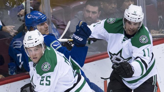 Dallas Stars' Brett Ritchie (25) and Curtis McKenzie (11) put Vancouver Canucks' Chris Tanev (8) into the boards during the second period of an NHL hockey game Saturday, March 28, 2015, in Vancouver, British Columbia. (AP Photo/The Canadian Press, Jonathan Hayward)
