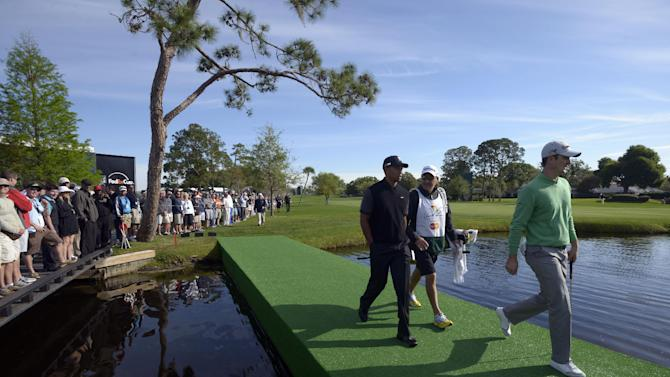 Justin Rose, right, of England, his caddie, Mark Fulcher, second from right, and Tiger Woods walk across a pond to the 16th green during the first round of the Arnold Palmer Invitational golf tournament in Orlando, Fla., Thursday, March 21, 2013.(AP Photo/Phelan M. Ebenhack)