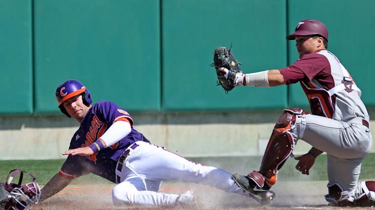 Clemson's Weston Wilson, left, scores a run as Virginia Tech catcher Andrew Mogg misplays the ball in the second inning of an NCAA college baseball game on Saturday, March 8, 2014, in Clemson, S.C., Saturday. March 8, 2014, in Clemson, S.C