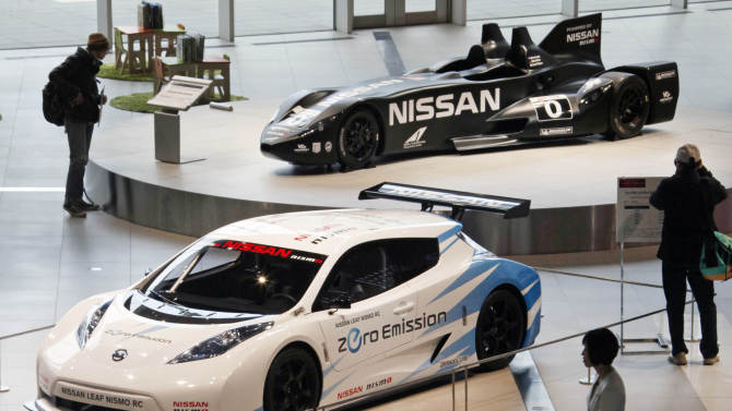 Visitors inspect Nissan electric cars at a gallery inside the headquarters of Nissan Motor Co. in Yokohama, Japan, Friday, Feb. 8, 2013. The Japanese auto maker suffered a 34.6 percent plunge in October-December profit to 54.1 billion yen (US$579 million) as global sales languished, especially in China, where anti-Japanese sentiment flared over a territorial dispute. (AP Photo/Koji Sasahara)