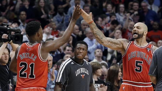 Chicago Bulls guard Jimmy Butler, left, celebrates with forward Carlos Boozer after scoring a basket, as Nate Robinson, center, watches during the second half of an NBA basketball game against the Miami Heat in Chicago on Wednesday, March 27, 2013. The Bulls won 101-97, ending the Heat's 27-game winning streak. (AP Photo/Nam Y. Huh)