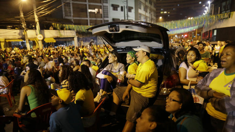 Brazilian soccer fans watch the Brazil vs. Cameroon match on a giant television screen in Bixiga neighborhood in Sao Paulo, Brazil, Monday, June 23, 2014. Brazil's Neymar scored twice in the first half to lead Brazil to a 4-1 win over Cameroon on Monday, helping the hosts secure a spot in the second round of the soccer World Cup. (AP Photo/Nelson Antoine)